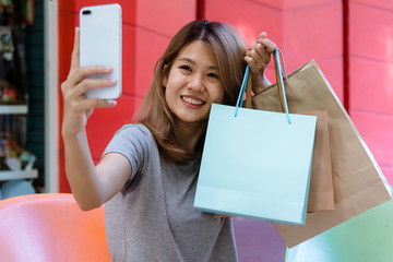 Young Asian woman taking selfie of herself with shopping bags after shopping in outdoor mall. Young woman and her city lifestyle on the weekend's morning. City lifestyle and outdoor shopping concept.