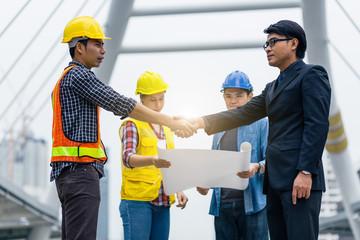 Handshake between engineer and manager, team meeting outdoor using blueprint