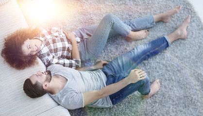 smiling couple lying on a carpet in a new apartment