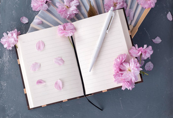 Sakura flowers and note book with a pen