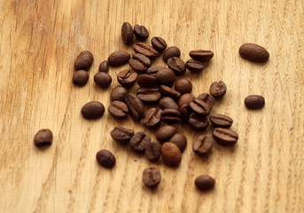 Coffee beans on wooden board with blur effect.