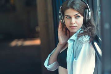 Young attractive girl listening to music indoors