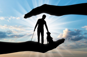 Silhouette of a blind disabled man with a cane in his hand and a dog guide