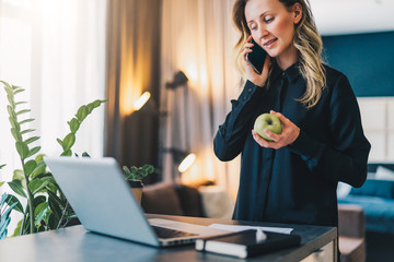 Young smiling businesswoman in black blouse is standing indoor near table in front of computer, while talking on cell phone and holding apple in her hands. Online marketing, education, distance work.