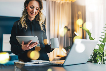 Young smiling businesswoman in black blouse stands near table in front of computer while drinking coffee, using digital tablet.Girl freelancer works at home. Online marketing, education, distance work