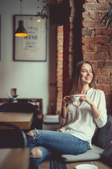 Young smiling girl with a cup of coffee