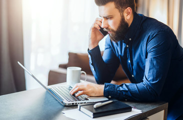 Young bearded businessman is sitting at table, working on computer, talking on cell phone. On desk notebook, documents. Freelancer works at home. Telephone conversations.Distance work,online education