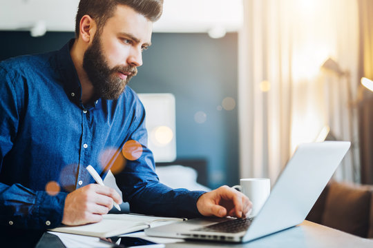 Young bearded businessman works on computer, takes notes in notebook, analyzes information, makes business plan. Freelancer, entrepreneur works at home. Online marketing, education for adults.