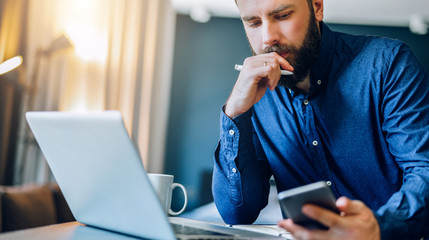 Front view. Young smiling bearded businessman sitting at table in front of computer, using smartphone. Freelancer, entrepreneur works at home. Online marketing, education for adults, distance work.