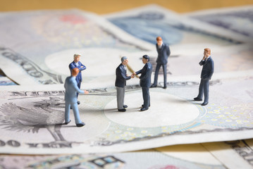 miniature businessman standing and shaking hand on Japanese banknotes