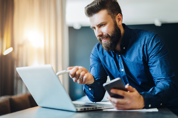 Young bearded businessman is sitting in front of computer, holding smartphone and showing pen on laptop screen. Freelancer, entrepreneur works at home. Distance work, online education, marketing.