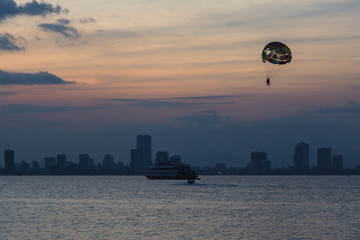 flight on a parachute behind a boat on the sea