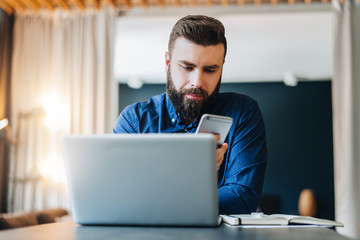 Front view. Young smiling bearded businessman sitting at table in front of computer, using smartphone. Freelancer, entrepreneur works at home. Online marketing, education for adults. Social network.