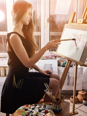 Artist painting on easel and palette in studio. Authentic girl paints with oil brush in morning sunlight dawn light toning window background. Flowers with watercolor. Sun flare and drawing homework.