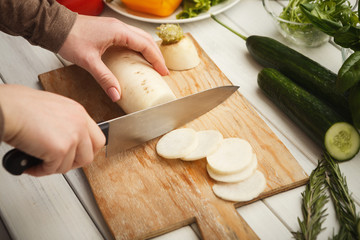 Woman cutting fresh turnip on wooden board