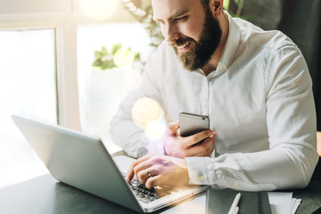 Young bearded businessman is sitting at table, working on computer holding smartphone. Man checking email, planning.