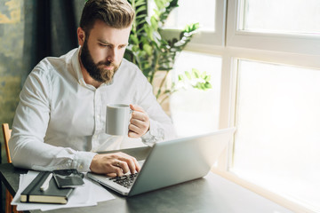 Serious bearded businessman is sitting at table, working on computer, drinking coffee. Man checking email, planning.