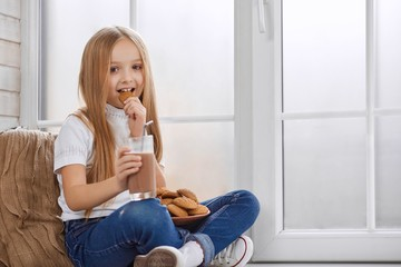 Pretty little girl eats cookies with chocolate milk. She sits near big white window. Child has big plate full of cookies on her hnees. Girl wears white sweatshirt and blue jeans with sneakers.