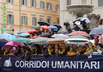 People wait to see Pope Francis after his meeting with the Community of Sant'Egidio, to mark the 50th anniversary of foundation, at Santa Maria in Trastevere basilica in Rome