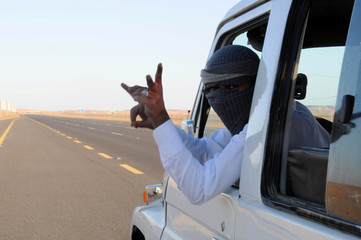 """Saudi man who performs a stunt known as """"sidewall skiing"""" gestures from his vehicle in Tabuk"""