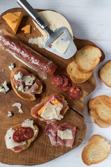 bread, meat, and cheese platter assortment on wood board top view