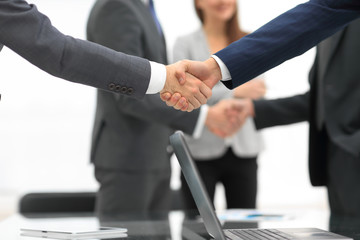 Men shaking hands with smile at office with their coworkers.