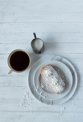 white pastry with coffee and cream on white flat lay