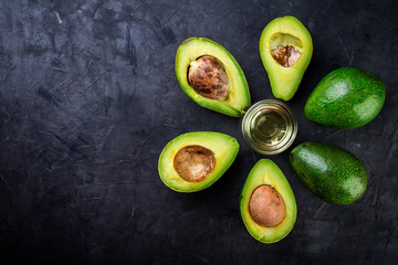 Fresh avocado  and avocado oil on a black background, top view