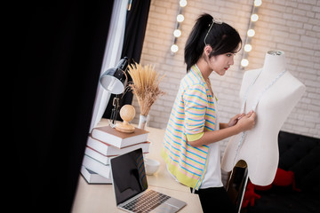 asian beautiful fashion designer  working at home with sketch book model stand