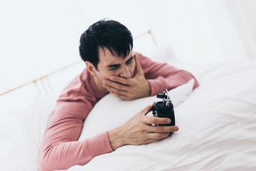smart caucasian man iw wakeup late  on bed with black alarm clock in white room background