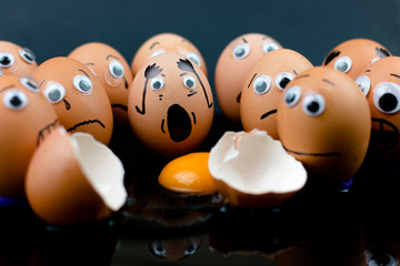 Fun concept: raw eggs with googly eyes and drawn features are in shock and sad as they witness another egg broken in two with the white and yolk in front of them; dark background.