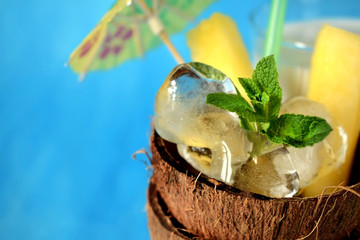 Ice cubes, mint and pineapple pieces in a coconut half. Ingredients for a tropical cocktail on blue background
