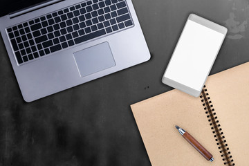 laptop smartphone notebook and wooden pencil stationary on black concrete table background with free copy space for your text