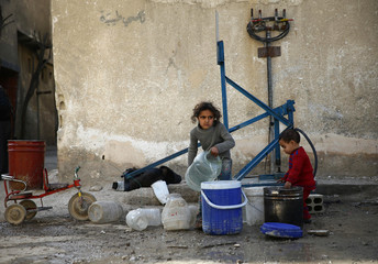 Children gather water in the besieged town of Douma, Eastern Ghouta, in Damascus