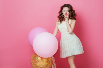 Cheerful Beautiful young girl in dress with sparkle and pink helium balloons enjoying birthday photoshoot dancing and smiling on pink background Surprised woman posing in studio. Fashion Lifestyle