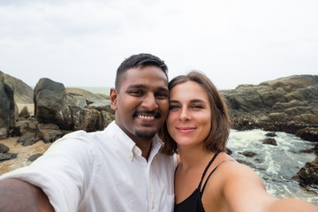 Young caucasian woman and asian man making selfie during honey moon in Sri lanka on beach. Concept of just married couple and true love