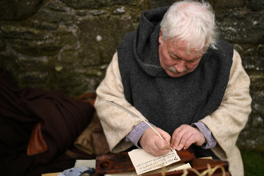 An actor playing a monk writes scripture during the re-enactment of the first landing of Saint Patrick in Ireland at Inch Abbey in Downpatrick