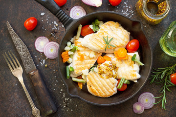 Grilled chicken fillet and various vegetables on a cast-iron frying pan, top view flat lay background.