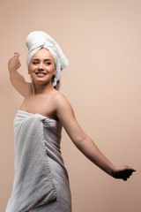 Sexy young cheerful beautiful woman after shower wearing white bathrobe and bath towel on head, happy girl doing exercises at home on pastel background.