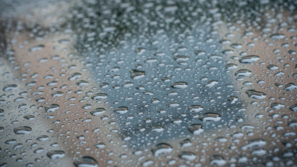 closeup of raindrops on black car