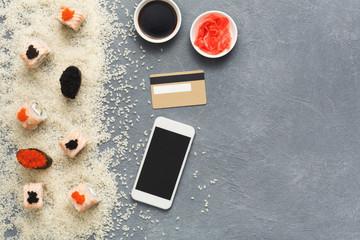 Sushi roll and gunkan near phone and credit card