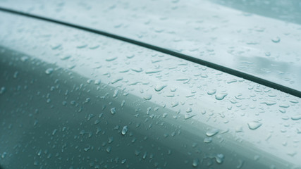 closeup of raindrops on green car