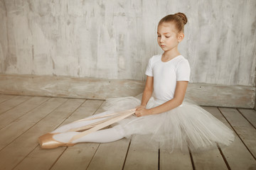 A little adorable young ballerina in white dress trying on her point shoes sitting on woody floor and gray studio background