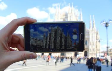 Turista al Duomo di Milano in Primavera: cellulare, guglie e statue