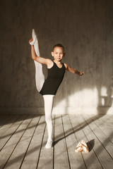 A little adorable young ballerina in black sportwear and white tights doing vertical split in the interior studio posing on camera in bright sunlight from window