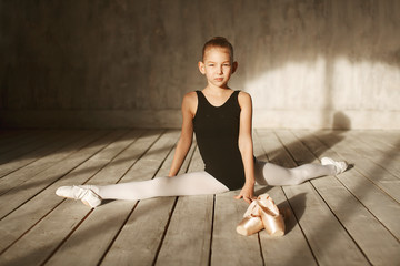 A little adorable young ballerina in black sportwear and white tights doing stretching in the interior studio posing on camera in bright sunlight from window