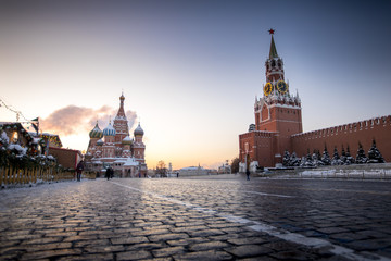Red Square comes to life on a cold winter morning with the sun rising behind St. Basil's Cathedral and the Kremlin