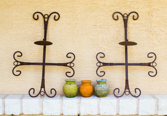 ceramic pottery and metal crosses decorating a townhouse patio