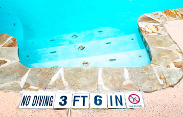 No Diving warning sign near swimming pool steps with limestone border