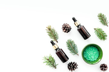 Pine spa cosmetics, products for skin care. Fir essential oil and green aromatic spa salt near branches and cones on white background top view copy space